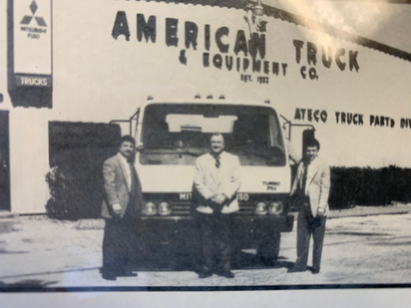 historical american truck and equipment building with 3 employees in front of a truck